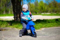 Motocyclette de jouet d'équitation de petit garçon en parc ensoleillé vert Photo stock