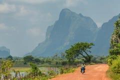 Motocyclette de monte de personnes birmannes locales sur la route de campagne près de Hpa-an, Myanmar Photos stock