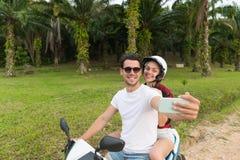 Motocyclette, homme et femme d'équitation de couples prenant le voyage de Selfie sur le vélo sur Forest Road tropical Photos stock