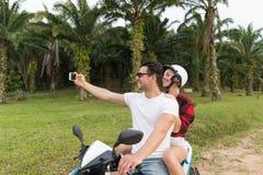 Motocyclette, homme et femme d'équitation de couples prenant le voyage de Selfie sur le vélo sur Forest Road tropical Image libre de droits