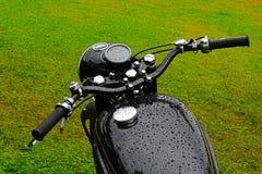Motocyclette humide noire de cru Photographie stock libre de droits