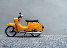 Motocyclette jaune par le mur gris Image libre de droits
