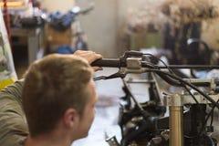 Motocyclette réparant par le jeune homme beau dans sa bordure de garage Photographie stock libre de droits