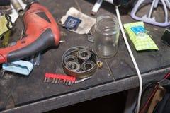 Motocyclette réparant par le jeune homme beau dans sa bordure de garage Photographie stock