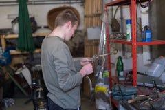 Motocyclette réparant par le jeune homme beau dans sa bordure de garage Photos stock