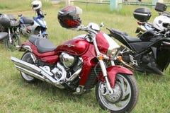 Motocyclette rouge garée de Suzuki Boulevard M109R sur l'herbe verte Photos stock