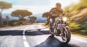 Motocyclette sur l'équitation de route avoir l'amusement montant la route vide o Photographie stock libre de droits