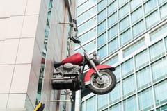 Motocyclette volant d'un bâtiment Photographie stock libre de droits