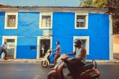 Motocyclettes conduisant les murs bleus passés des maisons historiques de la ville indienne Photos libres de droits
