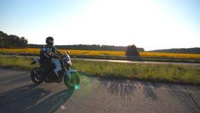 Motocycliste conduisant sa moto sur la route de campagne avec le gisement de tournesol au fond Jeune homme dans l'équitation de c clips vidéos