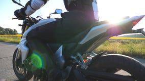 Motocycliste conduisant sa moto sur la route de campagne pendant le coucher du soleil Équitation de jeune homme sur un vélo de mo clips vidéos