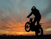 Motocycliste dans le coucher du soleil Image stock