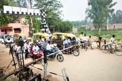 Motocyclistes, pousse-pousse, cyclistes attendant sur le croisement de chemin de fer photographie stock libre de droits