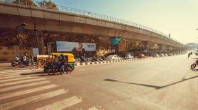 Motocykle i autorickshaw jeżdżenia past ogromny most z pojazdami w ruchu drogowym Zdjęcie Royalty Free