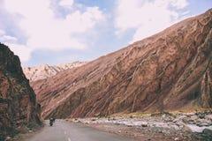 motocykliści na drodze między skalistymi górami w Indiańskich himalajach, zdjęcie royalty free