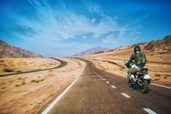 Motocyklista śpieszy się wzdłuż malowniczej pustynnej halnej autostrady obrazy stock