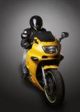 Motocyklista w hełmie na żółtym motocyklu zdjęcie royalty free