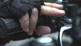 Motocyklista wręcza dosunięcie przerwy na handlebar zamkniętym w górę Samiec ręki w moto rękawiczkach trzyma przerwy na kierownic zbiory