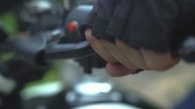 Motocyklista wręcza dosunięcie przerwy na handlebar zamkniętym w górę Samiec ręki w moto rękawiczkach trzyma przerwy na kierownic zbiory wideo