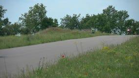 Motocyklisty setkarz przyśpiesza przy rasą Bawi się rower i pilota w rzemiennych kombinezonach na biegowym śladzie Rywalizaci ras zbiory wideo