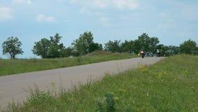 Motocyklisty setkarz przyśpiesza przy rasą Bawi się rower i pilota w rzemiennych kombinezonach na biegowym śladzie Rywalizaci ras zdjęcie wideo