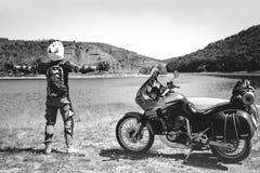 Motocyklu kierowcy stojaki z jego rękami szeroko rozpościerać dla spotkania przygody na brud plaży halnej rzece, enduro, dale zdjęcia royalty free