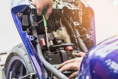 Motocyklu mechanik zamienia baterię utrzymanie selekcyjny Zdjęcie Royalty Free
