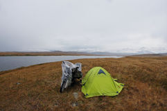 Motocyklu samotnego podróżnika pobliski zielony namiot przy ciemnej ponurości mgły stepowym brzeg jezioro fotografia stock