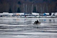 Motoneige solitaire sur un lac congelé Photographie stock