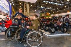 Motopark-2015 (bikePark-2015) Jonge paarbezoekers die in rolstoelen tentoonstellingstribune met motorfietsen en ATVs kijken stock foto's