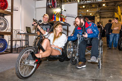 Motopark-2015 (BikePark-2015). People in wheelchairs are talking with the girl on the original bike (Handmade). Stock Photo