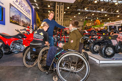 Motopark-2015 (BikePark-2015). Young couple visitors in wheelchairs looking exhibition stand with motorcycles and ATVs. Winter 2015. Morning. Russia. Moscow Stock Photos