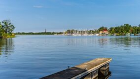 Free Motor And Sail Boats Anchored On The Lake Lagoon Pier Or Dock With Green River Reeds And Tries Royalty Free Stock Images - 177249669