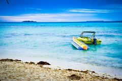 Motor and banana boats in the green sea water ocean under blue cloudy sky stock photo