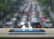 Business delivery service concept. Motor bike icon  on modern smart phone screen on wooden table over blur of rush hour with cars and road, Business delivery Stock Photo