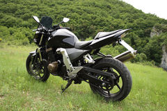 Motor bike parked in a field. Black modern motor bike  parked in a field using its metal stand with a background of bushes, trees and rocks Stock Photography