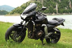Motor bike parked in a field Royalty Free Stock Image