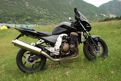 Motor bike parked in a field. Black modern motor bike  parked in a field using its metal stand with a background of bushes, trees and rocks Stock Image