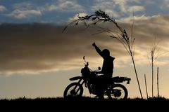 Motor Biker Silhouette at Sunset. Giving the thumbs up Royalty Free Stock Photography