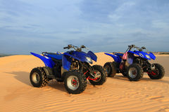 Motor Bikes. Four Wheels Blue Motor Bikes at Sand Dune Royalty Free Stock Images