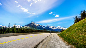 Motor Bikes driving the Duffey Lake Road surrounded by snow covered mountains. Motor Bikes driving Highway 99, also called The Duffey Lake Road, as it winds its Royalty Free Stock Photos