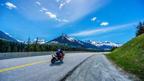 Motor Bikes driving the Duffey Lake Road surrounded by snow covered mountains. Motor Bikes driving Highway 99, also called The Duffey Lake Road, as it winds its Stock Images