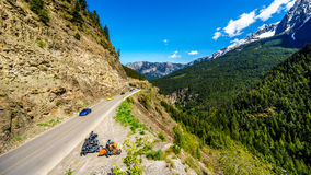 Motor bikes and fast cars driving the Duffey Lake Road surrounded by snow covered mountains. Motor bikes driving Highway 99, also called The Duffey Lake Road, as Royalty Free Stock Photo