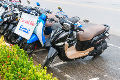 Motor bikes for rent in Ao Nang, Krabi. AO NANG, KRABI, THAILAND - 14 OCT 2014: Row of motorbikes for rent to tourists for transportation parked on an urban road Royalty Free Stock Images
