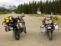 Motor bikes well equipped for a road trip parked at a rest area in northern canada. Dusty bikes loaded with survival gear resting before continuing towards Stock Photos