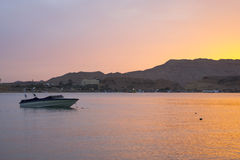 Motor boat is anchored among the Bay, evening sunset on the beac Stock Photos