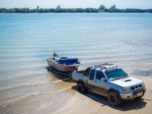 Motor boat being pulled with the pickup truck trailer on the beach.  royalty free stock images