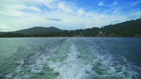 Motor boat departs from the town on a beautiful background of large green mountains stock footage