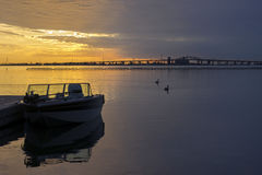 Motor boat docked silhouetted against a brilliant sunrise sky, b royalty free stock image