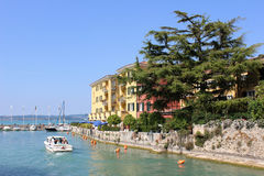 Motor boat entering harbor, Sirmione, Lake Garda Stock Photo
